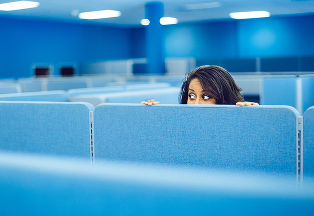 Female worker hiding behind cubicle wall