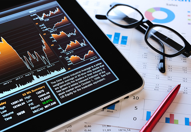 Financial analysis graphs in tablet and paper