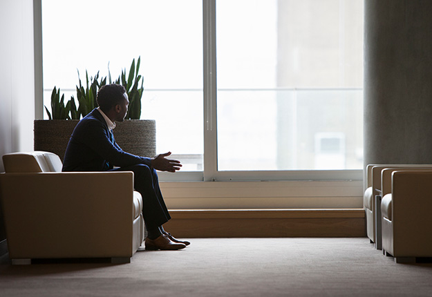 Businessman sitting down in lobby thinking