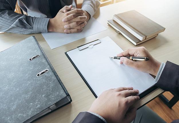 Businessman intervieweing a candidate resume on desk