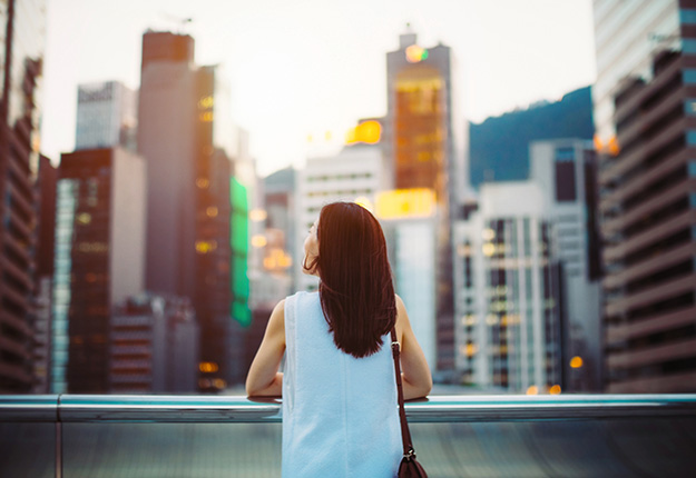 Woman looking up to buildings