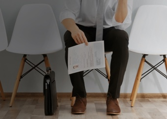 Man sitting down in a waiting room with his resume and briefcase