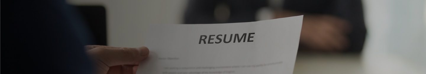A hand holding a resume. A buisiness person out of focus in the background.