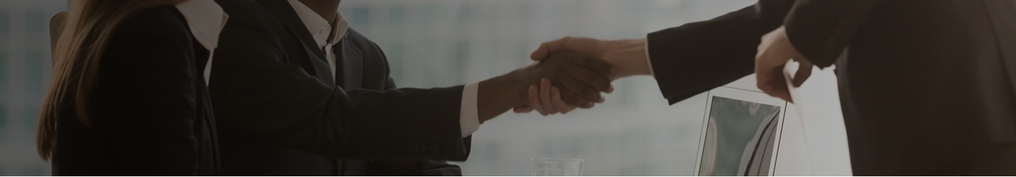 Two businesspeople shake hands in a conference room.