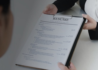 Woman handing over her resume on a clipboard to another businesswoman
