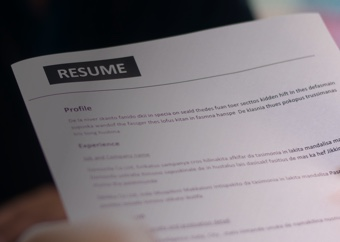 Hands holding a resume. A buisiness person out of focus in the background.