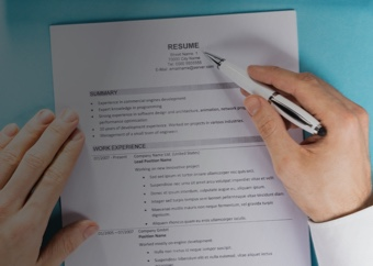 Male hands holding a resume and revising it with a pen.