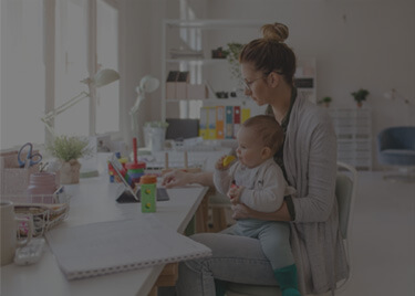 lady sitting with her baby and working