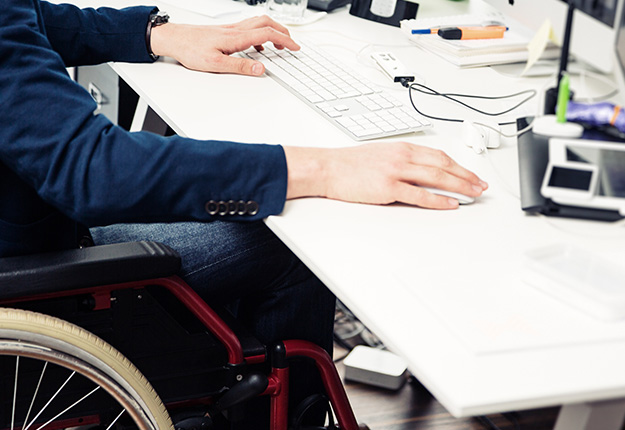 Businessman sitting on a wheelchair working
