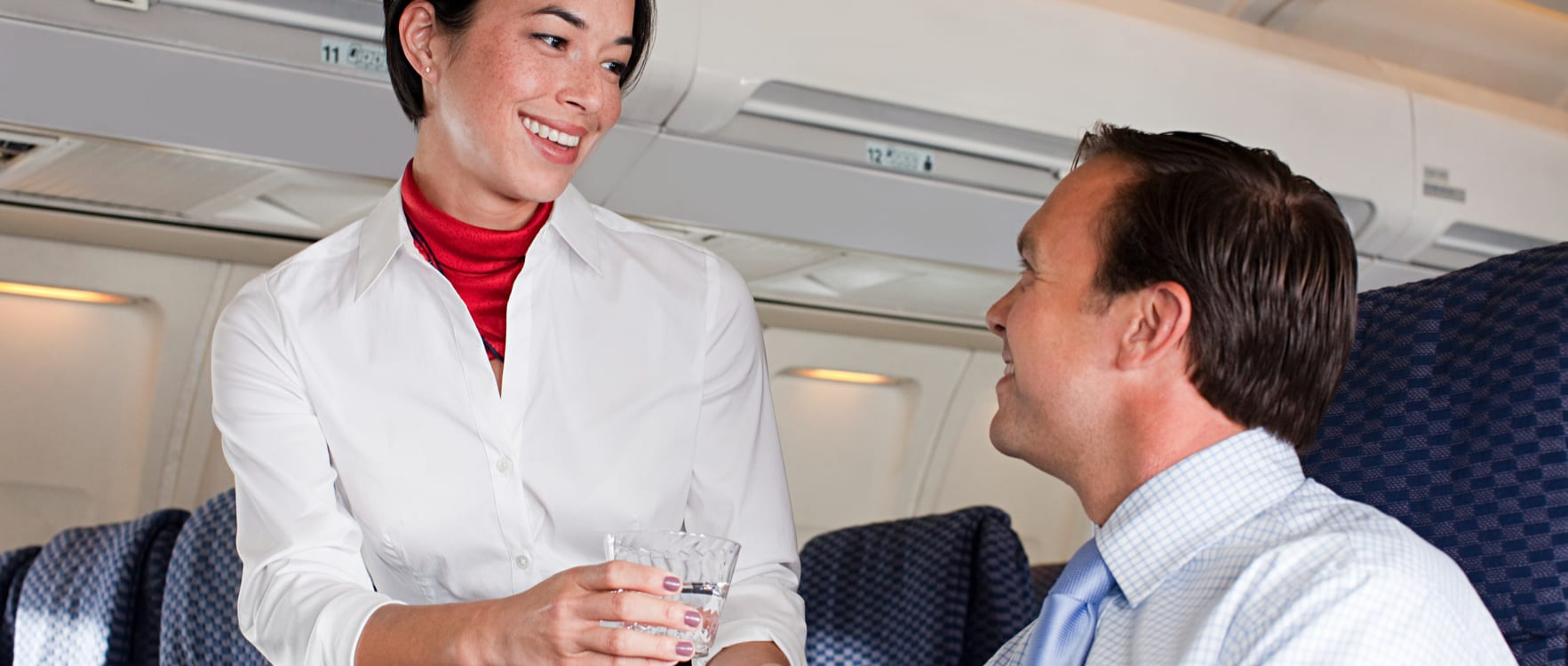 Air hostess serving a drink to a male passenger