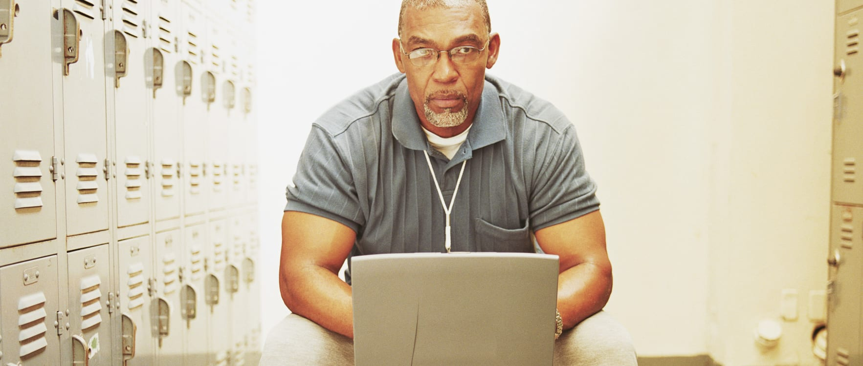 Middle-aged man working on a laptop in a locker room