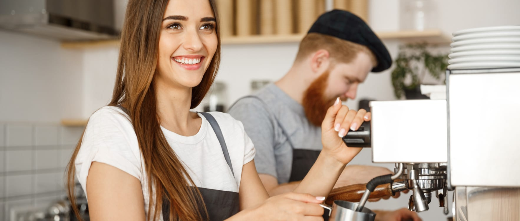 Barista couple working with a coffee maker