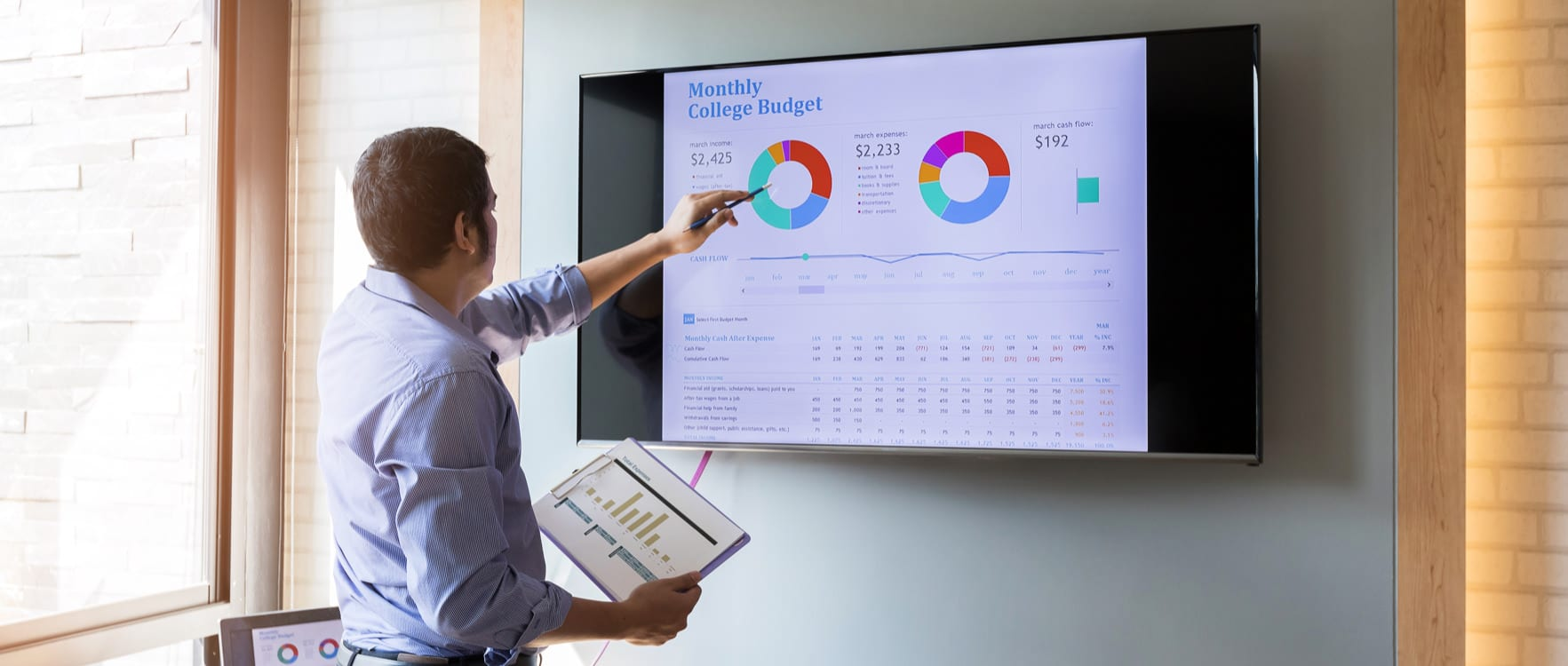 Businessman pointing at a monthly budget chart in a screen