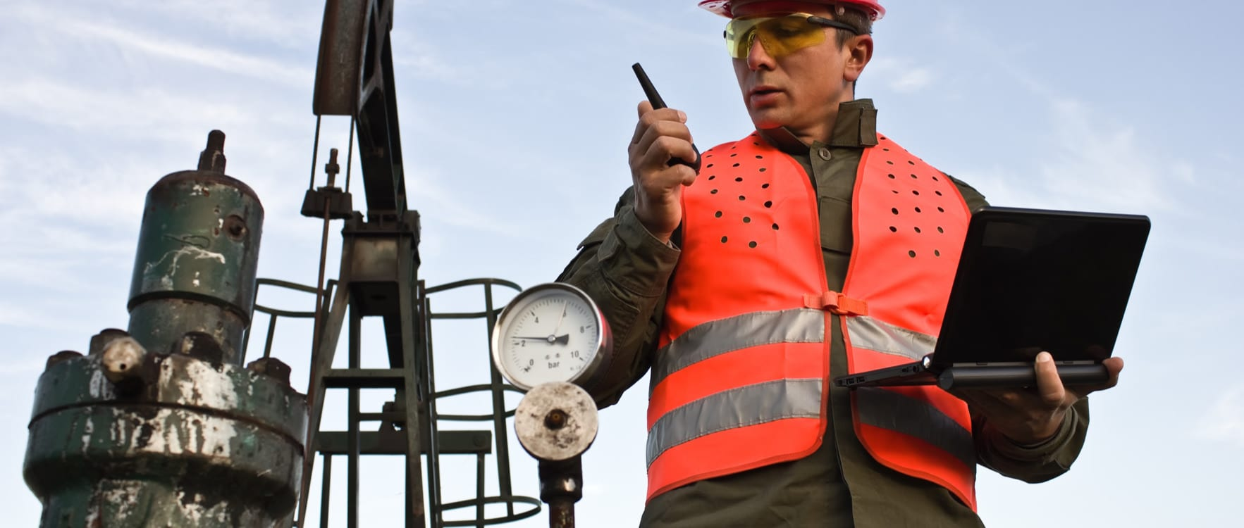 Man with safety gear inspecting a valve