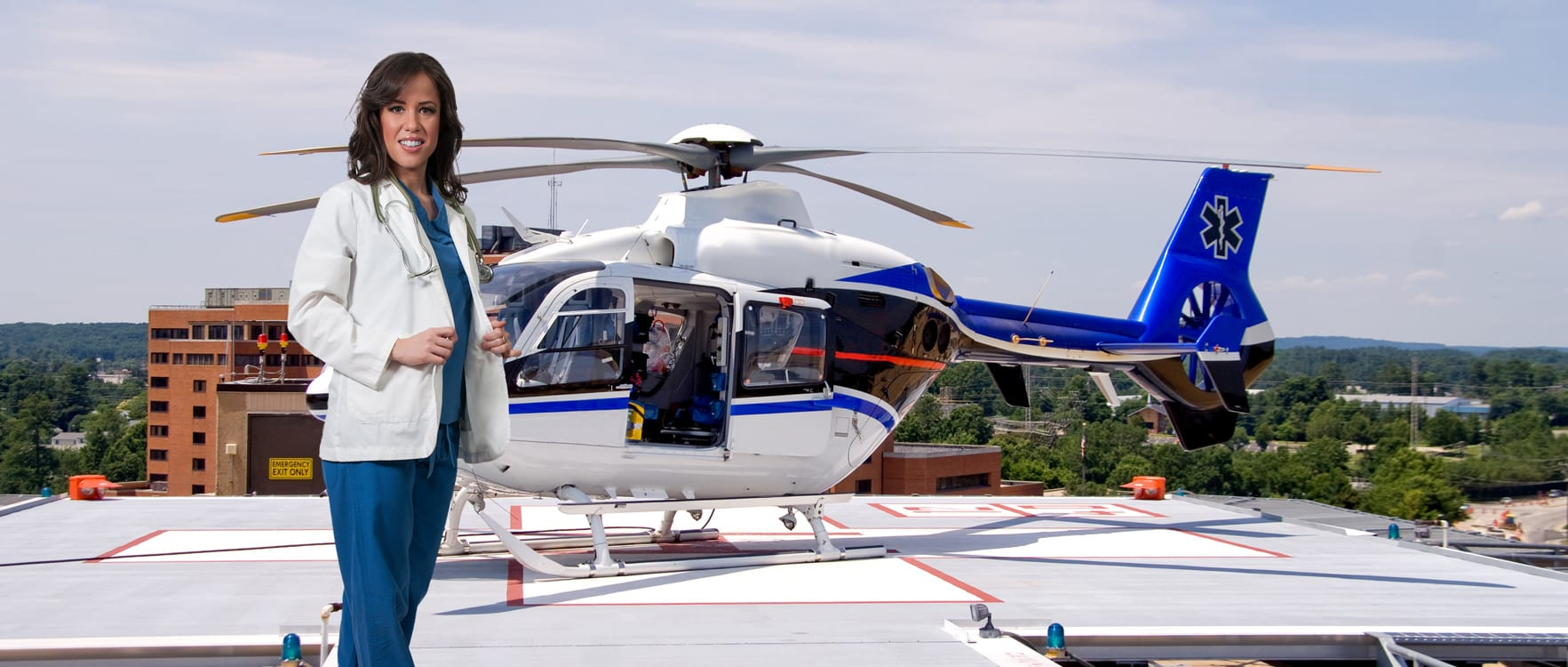 Nurse in scrubs standing in front of a helicopter