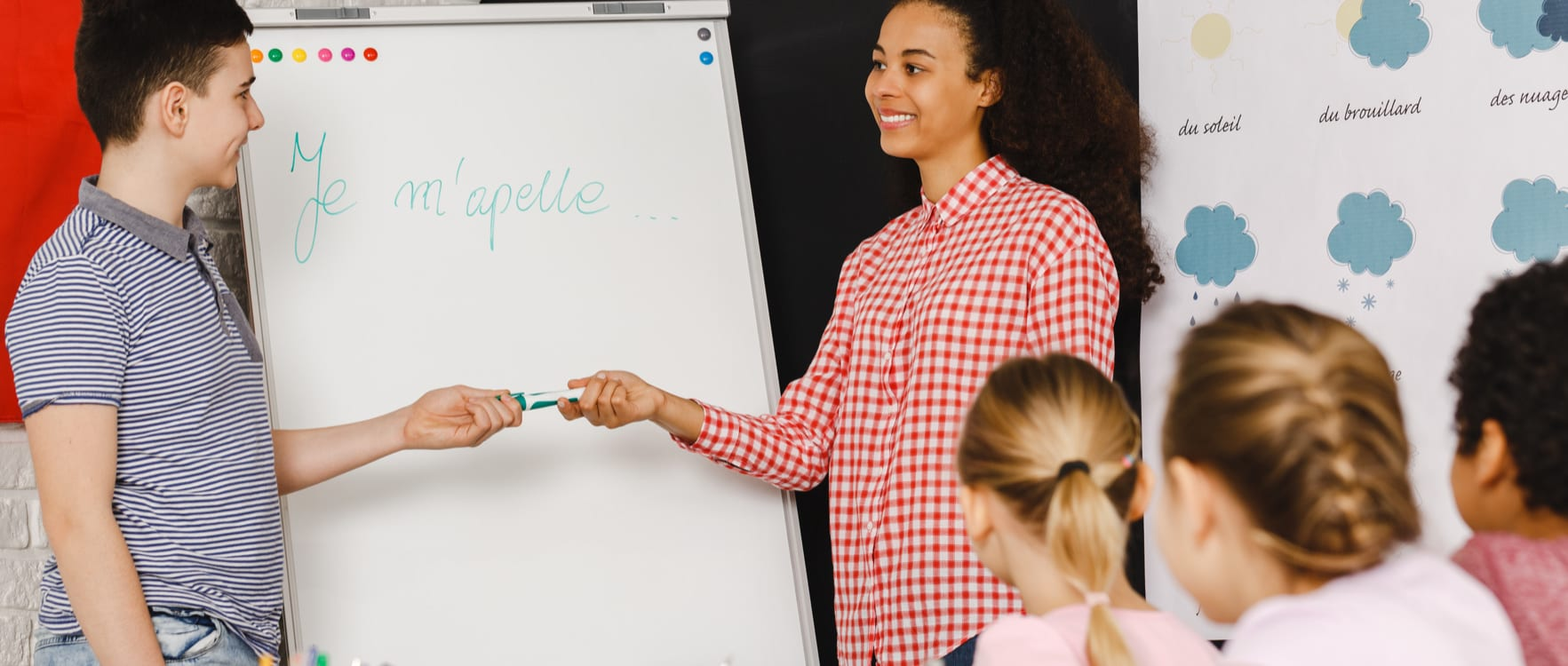 Woman teacher in front of a class handing a marker to one of her students next to a whiteboard with a written french word
