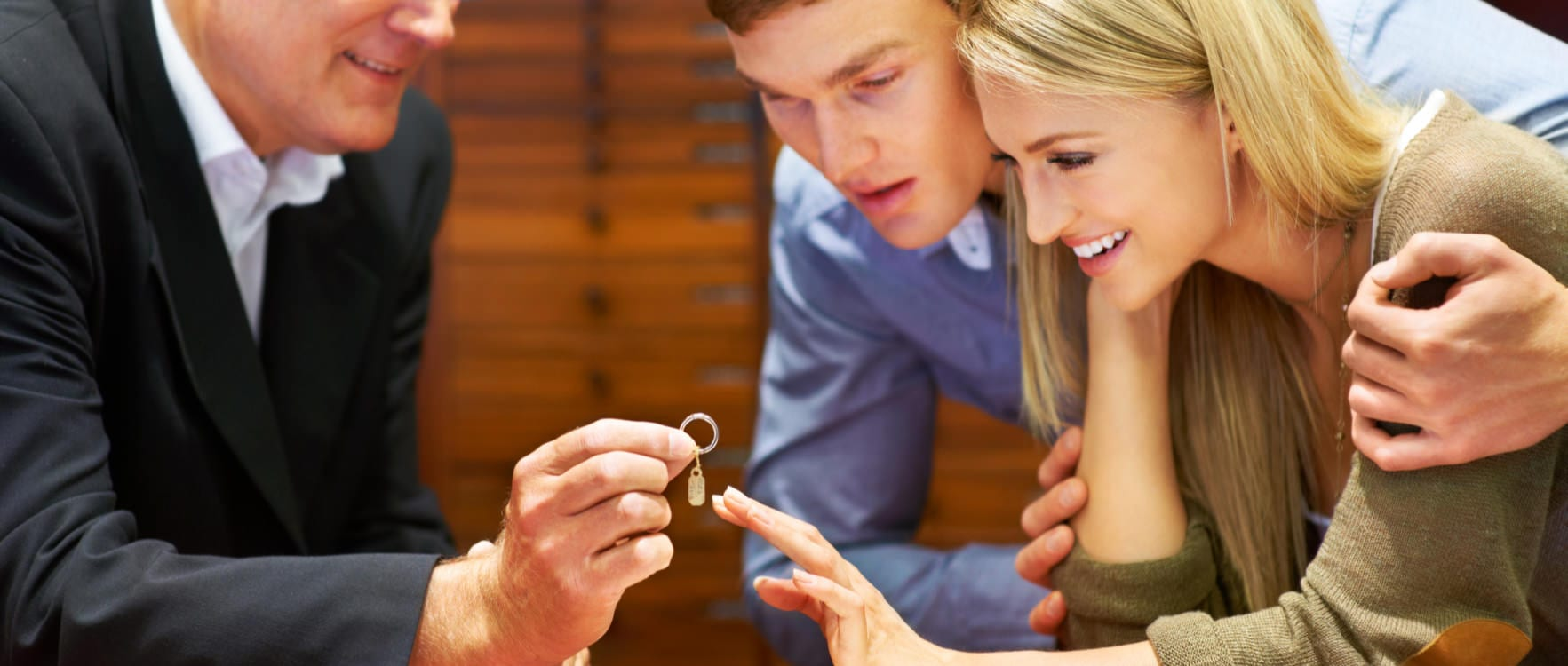 Jewel salesman showing a ring to a happy couple