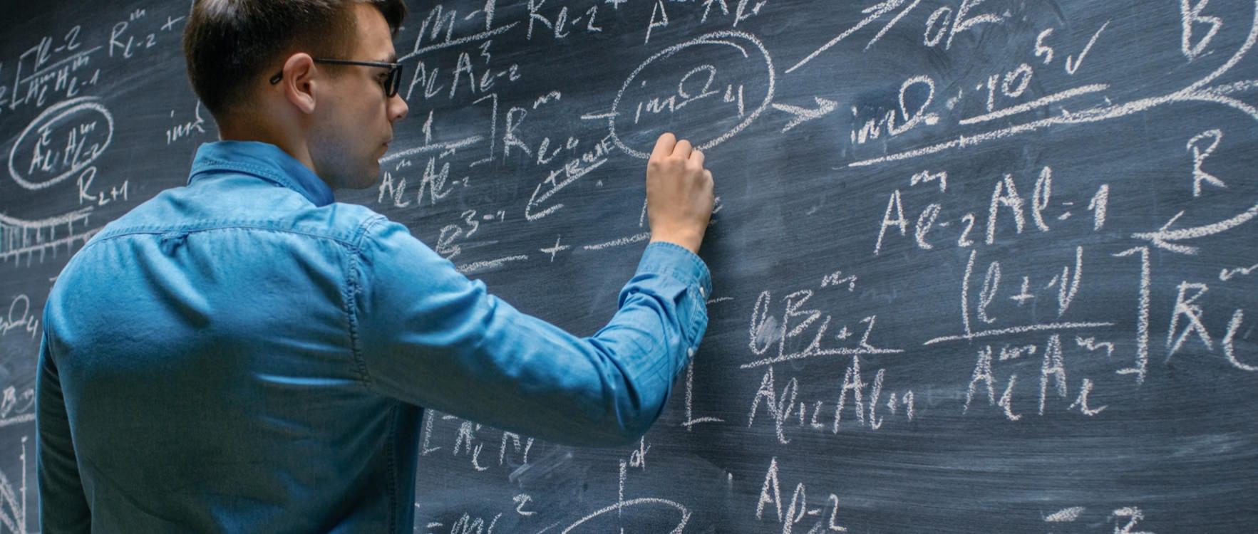 Man writing math equations on a blackboard