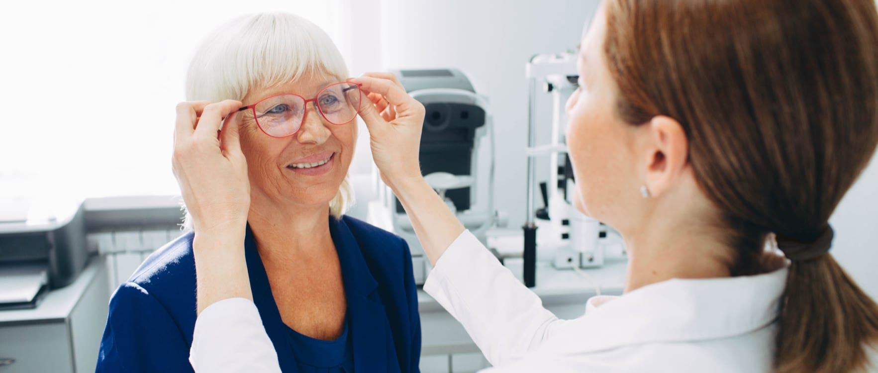 Female optician putting on glasses on a lady
