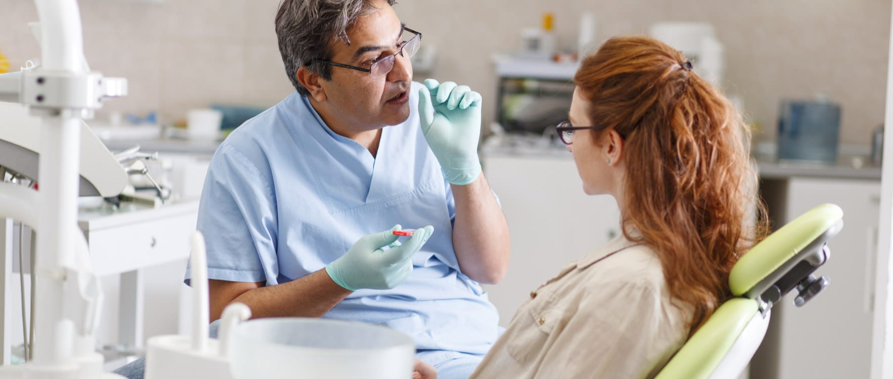 Male orthodontist talking to a female patient in an operating room