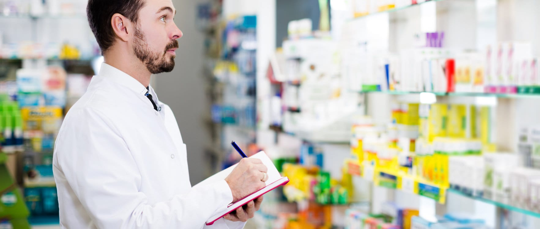 Male pharmacist taking notes while looking at medicine in the shelves of a pharmacy