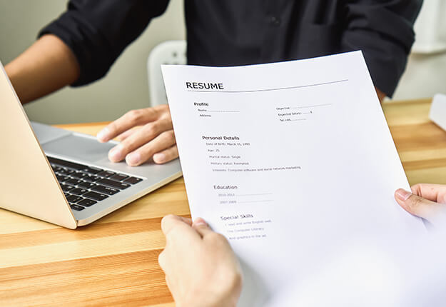 Person holding a resume. Man using a laptop