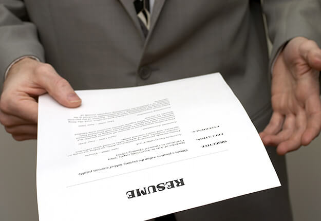 Man in a suit holding a resume