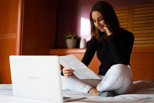 A woman sitting on her bed while holding her resume with her laptop open