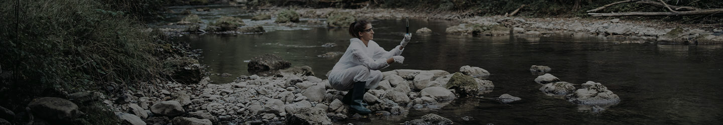 Scientist woman at a river collecting water samples