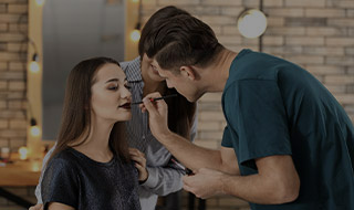 Male beauty technician applying makeup to a woman model