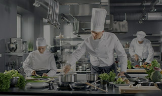 Group of prefessional chefs cooking at a kitchen