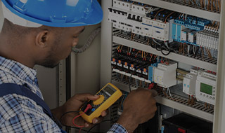 Electrician using a current meter on an electric panel