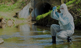 Scientist wearing an environmental suit taking a water sample from a river