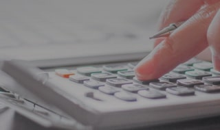financial advisor typing on calculator