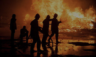 Silhouettes of firefighters putting out a fire at night