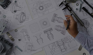 Engineer's hand holding blueprints of mechanical pieces